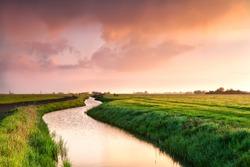 dramatic sunrise over canal in Dutch farmland, Groningen