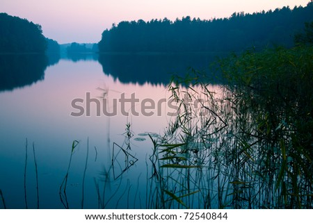 Dramatic sunrise over  quiet forest lake Seliger, Russia - stock photo