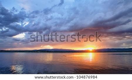 Dramatic sunrise over quiet lake