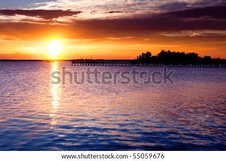 Dramatic sunrise over river pier. Indian river, Florida, USA