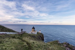 Dramatic sunset at St Abb's Head lighthouse in the Berwickshire, Scotland. Young freelance photographer is shooting a panorama landscape at the lighthouse during the sunset.