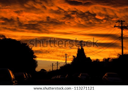 Dramatic sunset looking like a river of fire over an urban street with cars and streetlights