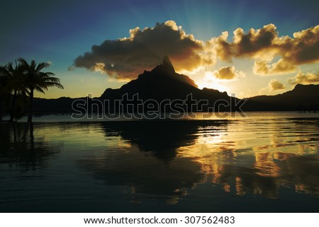 dramatic sunset on Mount Otemanu through lagoon and infinity pool on the tropical island Bora Bora, honeymoon destination, near Tahiti, French Polynesia, Pacific ocean