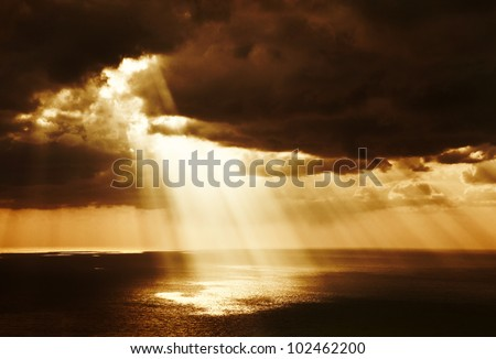 Dramatic sunset on the sea, beautiful peaceful scene, bright sun light, rays of light shine in water, sunbeam in cloudy sky, summer ocean view, paradise beach