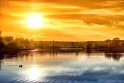 dramatic sunset over pond water with sky sun and outdoor scenery reflection on lake surface landscape view of summer river nature dusk background sunrise with sun above horizon at dawn time wallpaper