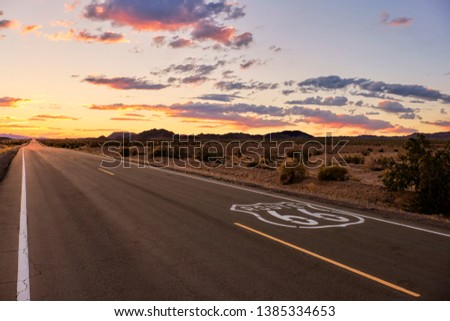 Dramatic sunset over route 66 with the open road going into the Mojave Desert while on a vacation road trip in Southern California. #1385334653