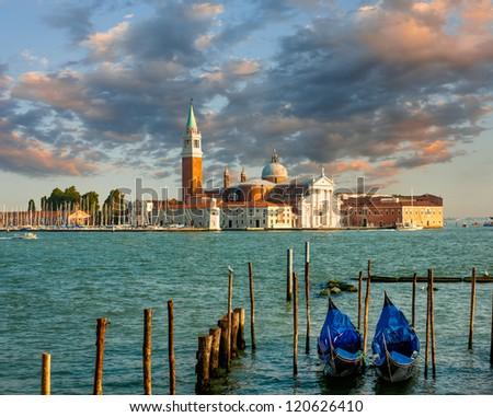 Dramatic sunset over San Giorgio Maggiore island with gondolas in front, Venice, Italy