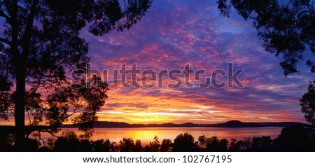 Dramatic sunset over water framed by trees at Woy Woy, near Sydney Australia
