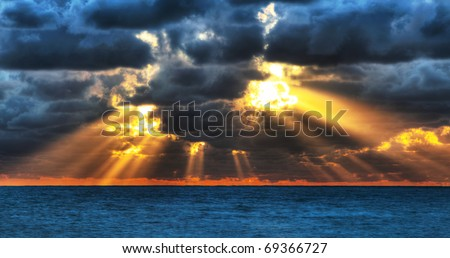 Dramatic sunset rays through a cloudy dark sky over the ocean.