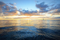 Dramatic sunset sky above the sea. Colorful glowing golden clouds, still water surface texture close-up. Sailing after the storm, view from the yacht. Epic seascape. Nature, fickle weather