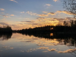 Dramatic sunset sky, clouds reflect in still water surface of forest lake, bare trees silhouetted on horizon