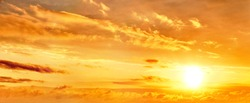 dramatic sunset sky landscape background. Natural color of evening cloudscape with setting sun. Orange clouds on yellow sky. Colorful panorama wallpaper. Ultra wide panoramic view. Banner template