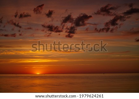 Dramatic sunset sky with clouds. Dramatic sunset over the sea