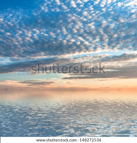 Dramatic sunset with clouds reflected in water.  #148272536