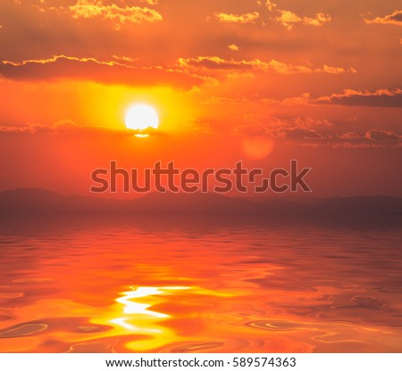 Dramatic sunset with clouds reflected in water. - Shutterstock ID 589574363