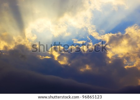 Dramatic sunset with golden sun rays among the clouds