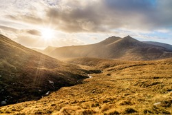 Dramatic sunset with sunrays in beautiful autumn coloured valley with river in Mourne Mountains, highest range in Northern Ireland