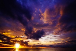 Dramatic threatening  sky clouds sunset after tropical rain thunder storm with bright sun star over ocean in horizon - Thailand, Ko Lanta (sunburst sun star effect)