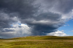 Dramatic thunderclouds over the tundra illuminated by the sunlight, Finnmark, Norway