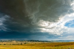 Dramatic thunderstorm over mountains and fields of rural Wyoming