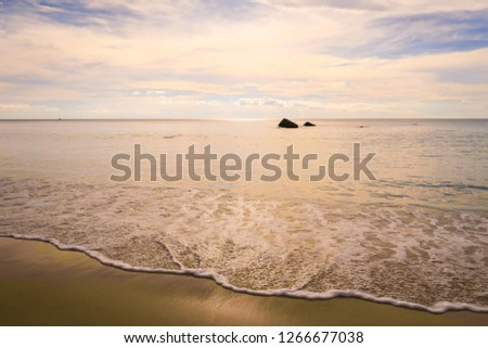 Dramatic twilight cloud sky over shiny sea water & soft waves touching the beach with small island on vintage style background, copy space. Natural landscape of sunlight & clouds-cape with calm ocean