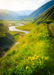 Dramatic vertical panoramic landscape view of  the mountains, river and cloudy sky with sun flare in the sky. Truso valley. Kazbegi. Travel in Georgia.2020
