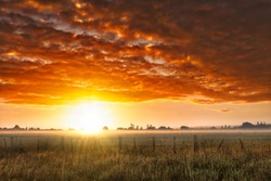 Dramatic vibrant cloudscape  at dawn over mist and fog with a sun flare on the horizon on the farm