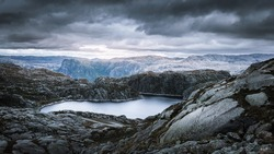 Dramatic view from the top of a mountain onto a mountain lake in front of a fjord, on a rainy September day in the norweigan highlands near Suleskard