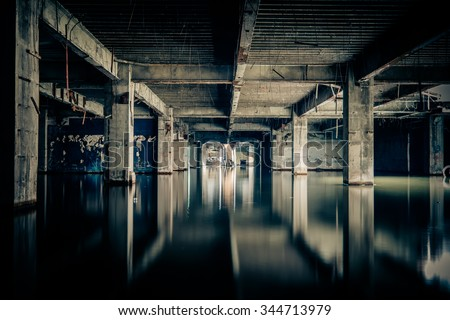 Stock Photo Dramatic view of damaged and abandoned building sunken by rain flood waters. Apocalyptic and evil concept