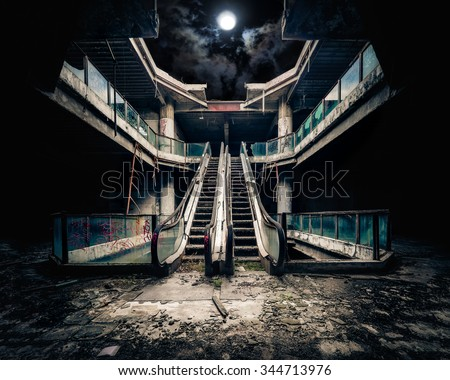 Stock Photo Dramatic view of damaged escalators in abandoned building. Full moon shining on cloudy night sky through collapsed roof. Apocalyptic and evil concept