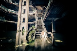 Dramatic view of damaged escalators in abandoned shopping mall sunken by rain flood waters. Apocalyptic and evil concept