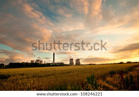 Dramatic view of Fiddler's Ferry coal burning power station, England. Cooling towers in the evening light with a cloudscape and field of wheat in the foreground