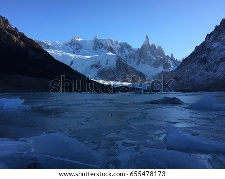Dramatic view of frozen lake and snow capped mountains in Patagonia Argentina against clear blue sky #655478173