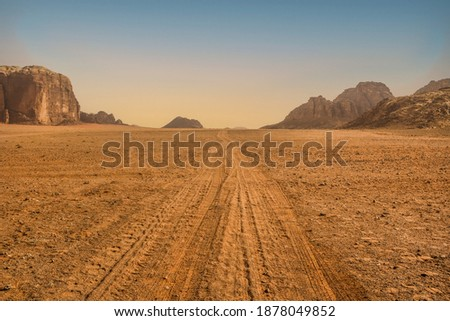 Dramatic view of the endless valley road, Wadi Rum desert, Jordania. Spectacular clear sky with yellow horizon line, mountain range, lots of red sand and extremely arid, dry terrain in the background. Foto stock ©