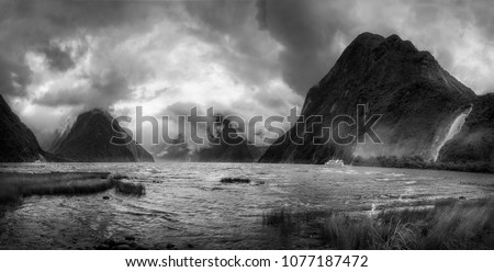 Dramatic weather conditions at Milford Sound in black and white, view at Freshwater Basin towards the fjord's entry, with Bowen and Stirling falls in Fordland National Park, New Zealand, South Island. #1077187472