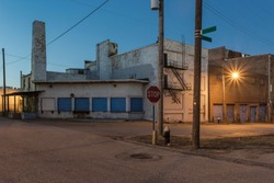 Dramatic wide angle Industrial street scene with brick buildings and blue freight doors in the evening with streetlight in a depressed blue collar urban area of St. Louis Missouri with clear sky