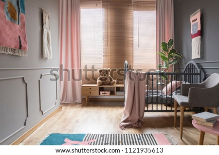 Drapes and blinds on windows in child's bedroom interior with pink blanket on bed. Real photo