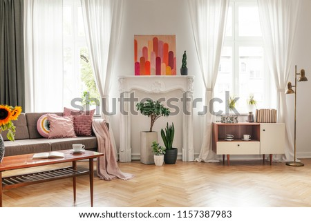Drapes at windows and poster in white living room interior with couch and cupboard. Real photo