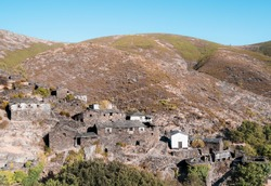 Drave, an abandoned village in a valley in Arouca, Portugal. Little stone houses on a hill surrounded by mountains