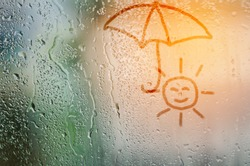 draw sun holding umbrella on natural water drops glass window background