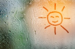 draw sun on natural water drops glass window background