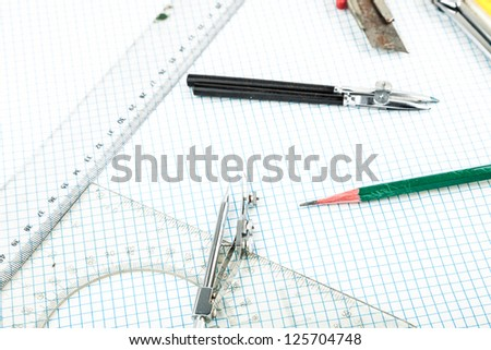 drawing compass , pencil, and ruler in the grid sheet studio shoot