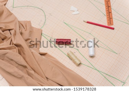 Drawing drawing for sewing clothes. Scissors, fabric, drawings and cutting on the table seamstress. Copyspace, flat lay.