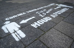 Drawing on pavement in Dutch letters means, 'We beat Corona together, this is 1.5 meters, keep your distance!' Coronavirus measures and rules for social distancing.