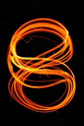 Drawing shapes with fire at night, infinity sign, bright colors on night background, fun with fire. Abstract fiery pattern in the shape of the number 8.