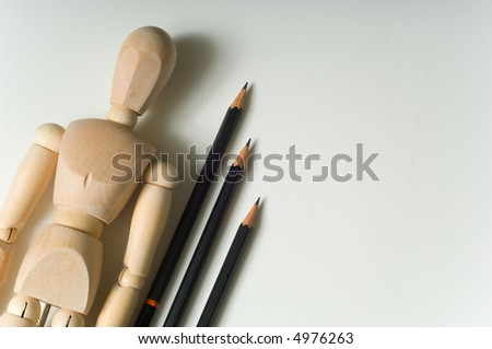 Drawing supplies including drawing pencils a wooden poser on a white sketch pad, the texture of the sketch pad is evident, great space for copy to the right