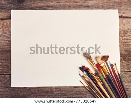 Drawing tools in art studio. Top view photo of paintbrushes and mockup of paper. Artist old wooden table with accessories.
