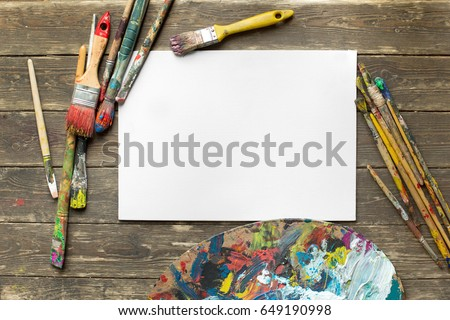 Drawing tools in art studio. Top view photo of paintbrushes next to palette with oil paints brushstrokes mixture and mockup of paper. Artist old wooden table with accessories. Creative concept