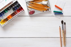 Drawing tools, stationary supplies, workplace of artist. Watercolor paints and blank paper on white wooden desk, top view, flat lay, copy space