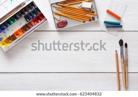 Drawing tools, stationary supplies, workplace of artist. Watercolor paints and blank paper on white wooden desk, top view, flat lay, copy space stock photo